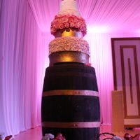 Wedding Cake Wedding cake adorned with floral details, hand piped details, zig zag pattern, sequins and nestled on top of wooden barrel decor.