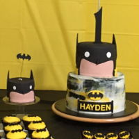 Batman. 1St Birthday Cake Buttercream blended yellow black & cream bottom tier with Batman symbol.Fondant Batman top tier. Black, flesh, yellow, white.Chocolate...