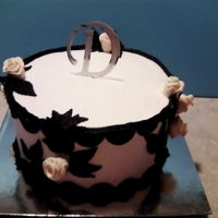 Black And White Cake Rum Chata flavored cake with bavarian creme filling, cream cheese frosting and modeling clay decorations.