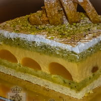 Diva Torte European style Torte. Dacquoise bottom layer, with apricot mousse, canned Turkish apricots and pistachio spongecake. Topped with Italian...