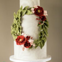Floral Wreath Cake A double barrel marble cake with a sugar flower marsala rose, pink hydrangea and mossy green leaves