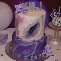 Geode Cake Two tiered cake; purple and white marbeled fondant, top hand painted with geode inset make with rock candy