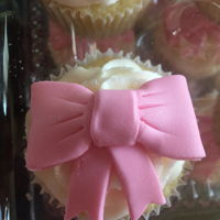 Pink Bow Pink bow baby shower cupcakes. White cake, raspberry filling, BC icing.