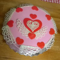 Sailor Moon Cake Pink round cake with angel wings and hearts.