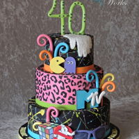 Totally Awesome 80's 40th birthday cake with splatter effect on the fondant. The accent elements are gum paste. The leopard tier was made with marvelous molds...