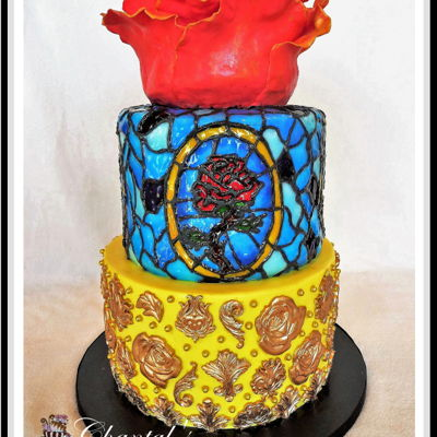Beauty And The Beast Three tiered cake. Top tier is a sculpted 6 inch tier. Petals are Magic Chocolate. Stained glass was created with royal icing, mirror glaze...