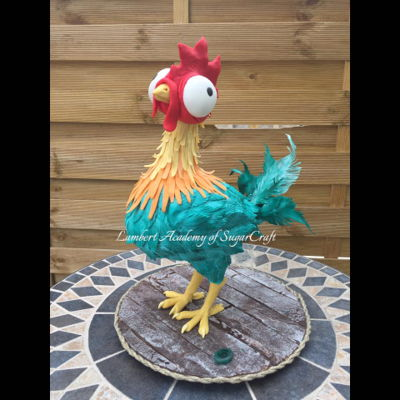 "Hei Hei 3D sculpted rooster stands 16"" tall and is constructed on a 12"" cake boardMaterials used: threaded rod armature, RKT, modelling..."