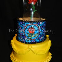 Beauty And The Beast Beauty and the Beast cake. Top tier outlined in royal icing, then painted with colored piping gel for the stained glass look.