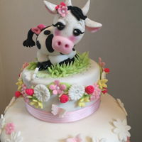 Cow-Themed Baby Shower Cake Two-tiered cake with fondant topper