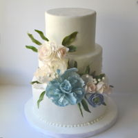 Floral Wedding Cake Three tier white wedding cake decorated with sugar flowers inspired by the wedding colours and the bridal bouquet. Flowers include peony,...