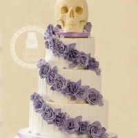 Skull Wedding Cake 3 tier wedding cake, decorated in white fondant with white chocolate drizzle, lilac roses and topped off with a massive solid white...