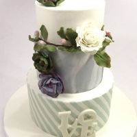 Wedding Cake With Succulents 3-tiered wedding cake with stripes and a marbled tier.