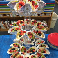 Fruit Taco Cookies Sugar cookie halves placed in cupcake papers, filled with sweet cream cheese fruit dip, and topped with fresh fruit. So yummy!
