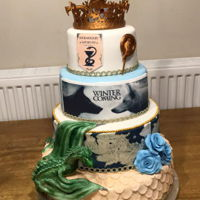 Game Of Thrones Tiered Celebration Or Wedding Cake. Game of Thrones cake, all edible apart from the 3d printed crown and sword made by my son.
