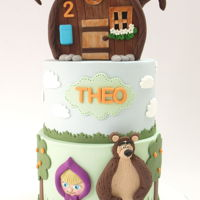 Masha And The Bear Very cute 2 tier cake with Masha and the bear theme. house topper made our of gumpaste. This was a second birthday celebration!