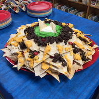 Nacho Cake Vanilla cake layered with buttercream frosting. Toasted cinnamon flour tortilla shells poked into the sides and covered with chocolate/...