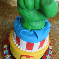 "Super Hero Tiered Cake 2 tier cake covered in fondant with fondant decorations and RKT fondant covered 'Hulk"" fist"