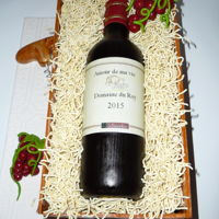 Wine Bottle In A Wood Box Wine bottle in a wood box. The bottle is fondant with an edible image. The straw is chinese noodles. The wood box is fondant.