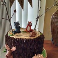 Woodland Animals Tree stump made with chocolate buttercream, Fondant woodland critters moose, raccoon, fox, hedgehog, Pennant string attached to twigs,...