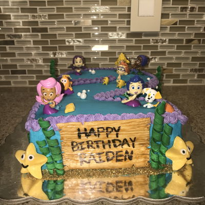 Bubble Guppies Buttercream Cake Bubble guppies buttercream cake for 2nd birthday. Figurines are plastic, shells are chocolate, seaweed,coral and wood sign are fondant.