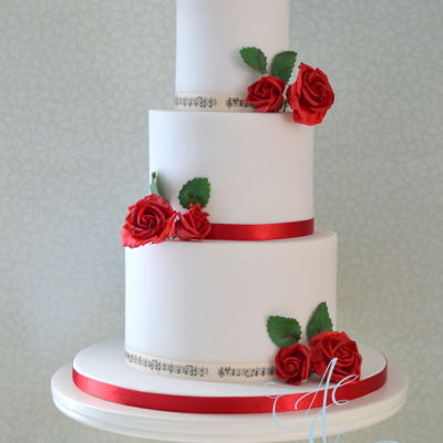 Gemma. Classic red roses wedding cake. Two tiers of Madagascan vanilla, one zesty lemon. The groom is in a rock band, hence the musical ribbon!