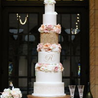 Gold, Lace And Floral Wedding Cake Gold variegated pearls, hand piped and painted monogram and edible lace on this giant beauty. Finished with beautiful fresh florals