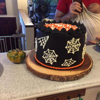 Halloween Cake Black chocolate cake with orange buttercream inside and black chocolate frosting outside. The top is halloween sprinkles