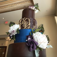 Peacock Themed Wedding, All Chocolate Cake. Sugar flowers and feathers on a chocolate and shimmery cobalt fondant. Chocolate cake inside with 4 different fillings- Black Forest,...