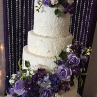"Purple And Lace Wedding Cake Multiple flowers in shades of purple with edible lace. 6"" 8"" 10"" 12"""