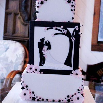 Black And White Silhouette Wedding 3 tier square fondant (12/10/8) with bride and groom silhouette on middle tier panel. Handmade whimsical flowers on bottom and top tiers....