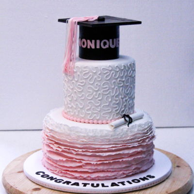 Graduation With Ruffles 2 tier fondant in shades of pink with handmade cap, scroll and tassel. Design inspired by customer provided photos.
