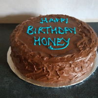 Birthday Cake Vanilla and chocolate cake covered with chocolate fudge icing