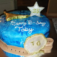 Cowboy Cake Fondant blue jeans, fondant belt buckle, belt, and cow head painted in luster dust.