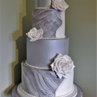 Elegant Marbled Wedding Cake 4 tiered wedding cake. Split white & marbled icing on 2 tiers and lustered grey/silver tiers. White handmade roses.