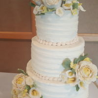 Ivory Wedding Cake With Yellow Accents And Ribbon Textured Buttercream The bride wanted daisies but many other flowers would look better (IMO), so we decided on ivory flowers with yellow accents. I did...