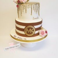 Michael Kors Fondant with fondant accents, royal icing drip hand painted gold. Gumpaste roses and filler flowers.