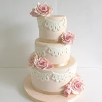 Quince Cake 3 tiers 9,7,5 all covered in an ivory fondant lace qpplique trim used marvlous mold fondant roses