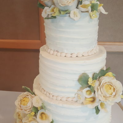 Ivory Wedding Cake With Yellow Accents And Ribbon Textured Buttercream