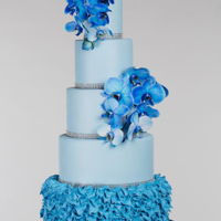 Blue Ivy All powder blue wedding cake with fresh blue orchid flowers and buttercream feathered design.