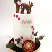 Cute Reindeer For Ana Double barrel cake for Ana´s birthday party. Sugar reindeer topper and a touch of color with sugar ranunculus and folliage.