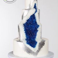 Geode Cake White cake with silver trimming around the geo design.