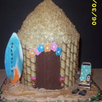Tiki Hut Modeling chocolate decorations with crushed shredded wheat roof, cookies surrounding building and toy chair.