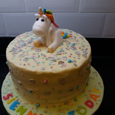 Unicorn Birthday Cake Made from layers of rainbow coloured sponge covered in butter icing. Unicorn made from fondant and sprinkles from Lakeland.