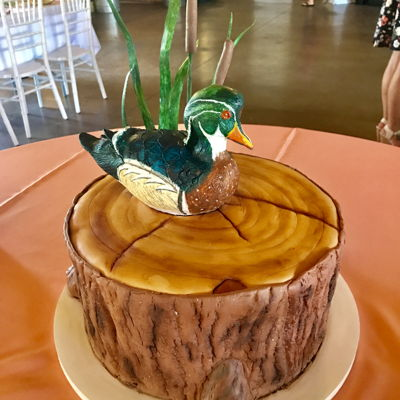 Wood Duck On Tree Stump Wood duck carved out of cake and covered in modeling chocolate. Then hand painted with petal dusts. Wafer paper grass, fondant cat tails,...