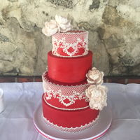 Bold Red And Delicate Lace Wedding The couple wanted to have a bold red wedding cake to go with their 50'S theme. The lace trim added retro touches and white peonies to...
