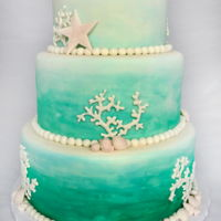 A Beach Themed Wedding A 3 tier White, Teal, & Coral beach themed wedding cake.