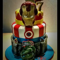 "Avengers Birthday Cake Multi-tier ""Avengers"" themed cake covered in fondant. Iron Man Mask, Hulk fist, and Thor's hammer are RKT..."