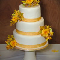 Autumn Leaves Wedding Cake with autumn leaves and orange roses.