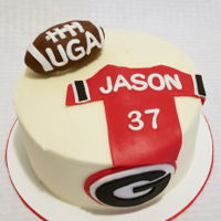 Uga Birthday Cookies and cream cake. Fondant jersey and logo, rice crispie treat football covered with fondant.