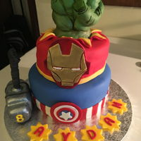 Avengers Birthday cake with Hulk fist Cupcakes with Avengers emblems.